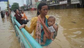 Seorang ibu yang sedang menggendong anaknya berjalan melewati genangan air. (C) http://media.viva.co.id/thumbs2/2013/01/16/188102_banjir-di-kampung-melayu_663_382.jpg