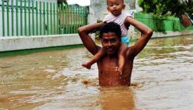 Seorang bapak memangku anaknya ditengah kondisi banjir. Terlihat banjir mencapai ketinggian perut dari orang dewasa. (C) http://media.viva.co.id/thumbs2/2010/02/14/85164_siaga_satu_banjir_jakarta_663_382.jpg